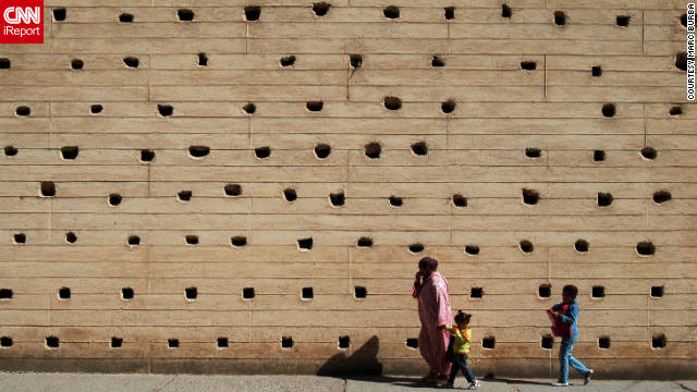 "Marc Burba shared a photo of this family walking past a high wall of the medina. ""The holes are used as birdhouses,"" he pointed out."
