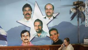 A government employee works next to a mural showing the Cuban Five in Havana in August 2005. Three of them remain imprisoned in the United States.