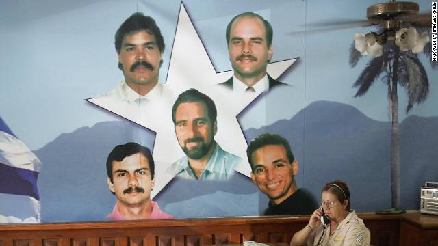 A government employee works next to a mural showing the Cuban Five in Havana in August 2005. One was released Friday.