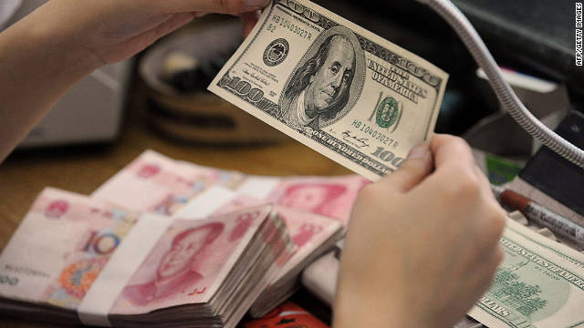 A Chinese bank worker checks a $100 bill together with stacks of 100 yuan notes at a bank in Hefei, east China. 