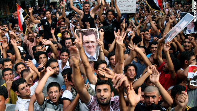 Syrian regime supporters carry pictures of President Bashar al-Assad during a protest in Beirut on 2 October.