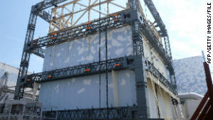A Fukushima Daiichi reactor building is covered by a steel frame to prevent dispersal of radioactive materials.