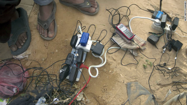 Bengladeshi refugees from Libya recharge their cellular telephones on March 9 at the Choucha camp in Tunisia near the border with Libya.