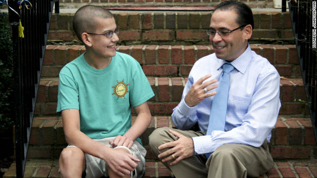 Dr. Carlos Zayas talks with Isaac del Valle at the del Valle house in Alpharetta, Georgia. Dr. Zayas, who battled cancer himself, helps other Hispanics find bone marrow donors.