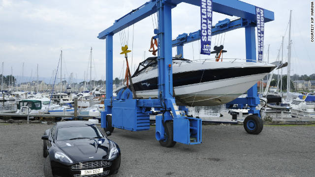 "The ""Quantum of Solace"" Sunseeker hoisted up on a transporter with James Bond's favorite car, an Aston Martin, alongside."