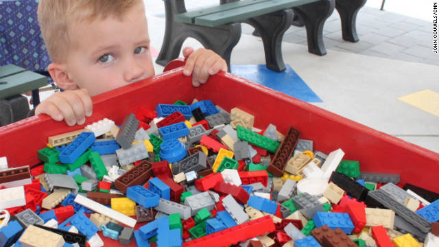 Three-year-old Cole Herbet crouches behind a big Lego bin while his grandparents buy annual passes to the new park.