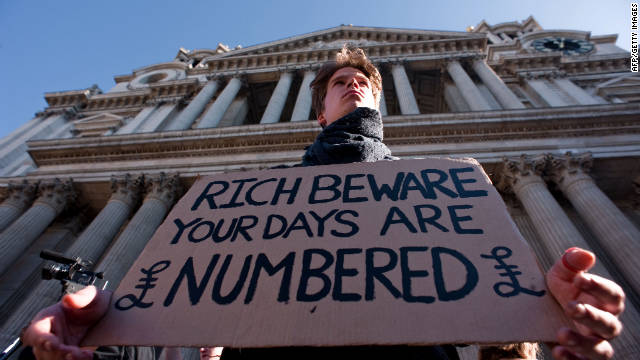 A protester stands on the steps of St. Paul's Cathedral in London on Saturday. WikiLeaks co-founder Julian Assange led the thousands of protesters in chants outside the church.
