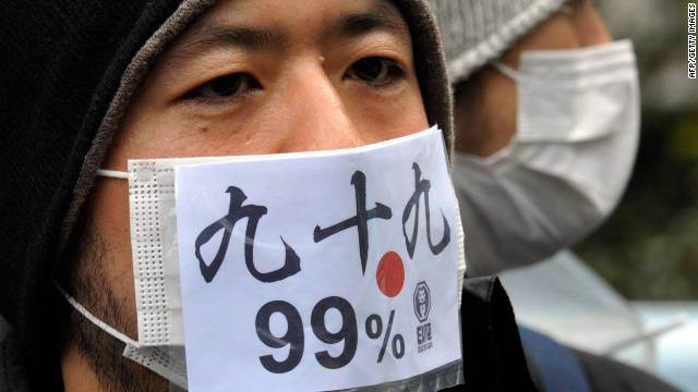 A Japanese protestor wears a mask that says &quot;we are 99 percent&quot; during a Saturday protest in Tokyo.