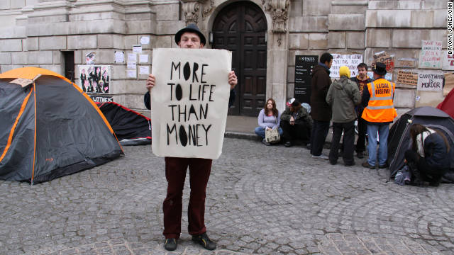"Occupy London protester James Banks holds up a poster reading ""More to life than money."""
