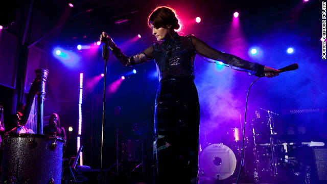Dressed in a sheer button-down shirt and long skirt, the flame-headed Florence Welch belts out new numbers.