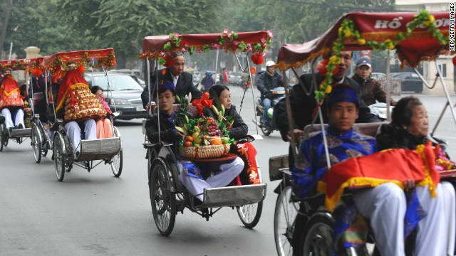 A convoy of cyclos carry a family members to a pre-wedding ceremony in Hanoi, Vietnam.