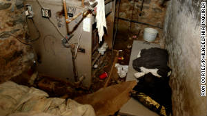 Police say the victims were locked in this dank sub-basement chamber that reeked of urine and excrement.
