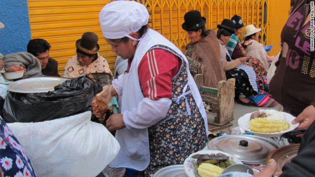 A woman serves plates of potatoes, corn, rice and meat. Markets throughout the city offer the chance to eat like a local.