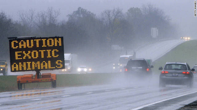A sign warns drivers of the exotic animals loose outside Zanesville, Ohio, on Wednesday, October 19. It appears that Terry Thompson, 62, released 56 animals and then died from a self-inflicted wound, an official said.
