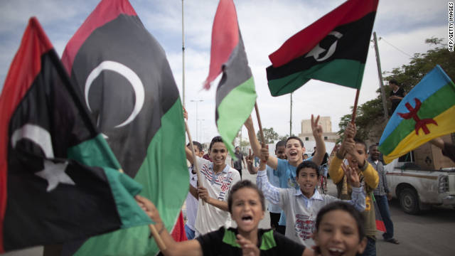 Kids wave National Transitional Council flags in Tripoli after news of Moammar Gadhafi's capture. He was later reported killed.
