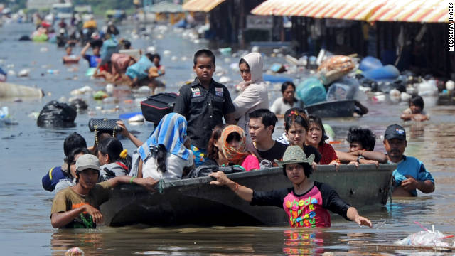 Thai residents walk through floodwaters as they are evacuated from their apartments in Pathum Thani province, suburban Bangkok, on October 19.