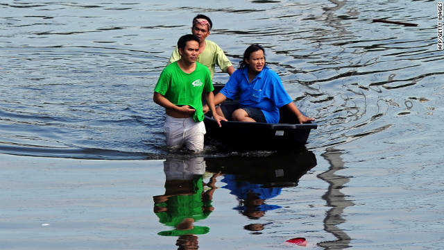 Bangkok residents cross flood waters as Thailand prepares for more rain.