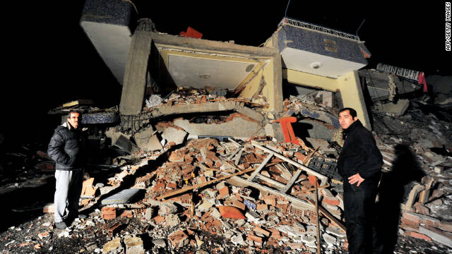 Two men stand in the rubble of a collapsed building in the aftermath of the quake on Sunday.