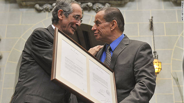 Guatemalan President Alvaro Colom, left, hands a letter of apology to the son of former president Jacobo Arbenz last week.