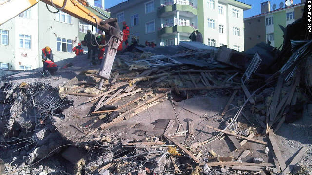 Rescue teams attempt to dig through the rubble of a collapsed building in Ercis looking for survivors.