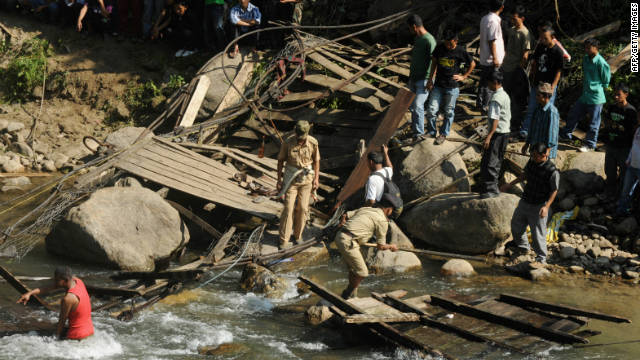 Indian villagers and rescuers gather at the scene of a bridge that collapsed on Saturday.