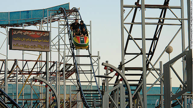 "Riders take the first plunge on one of Eram Park's ""rusting"" roller coasters."