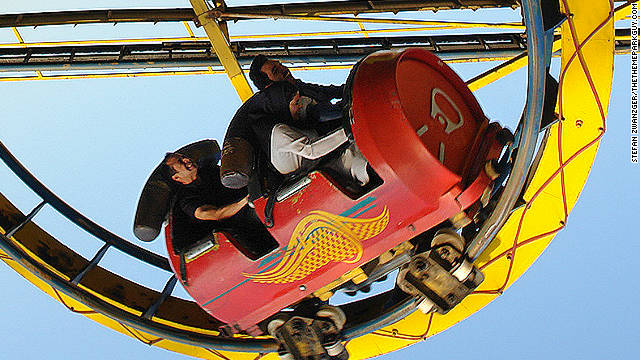 Riders grimace as the soda-can roller coaster negotiates a tight loop.