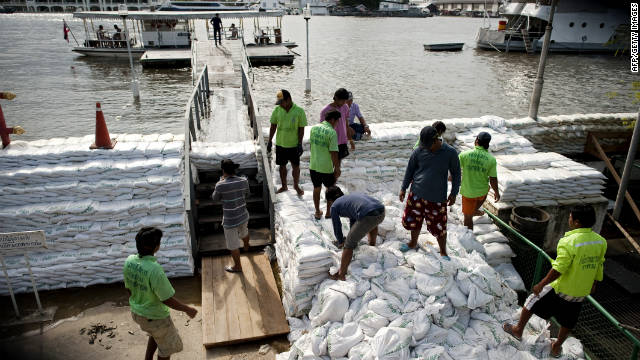 Workers construct a sandbag wall Wednesday along the Chao Praya River, anticipating that it would overtop its embankments over the weekend.