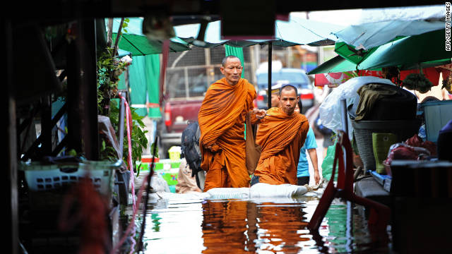 Buddhist monks walk toward a pier along the Chao Phraya River, which winds through the capital.