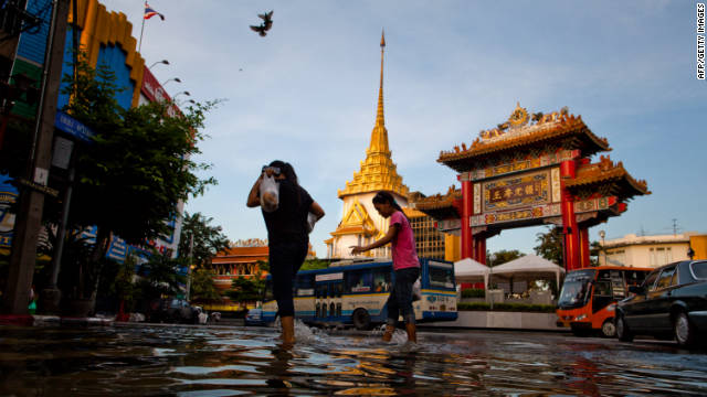 People walk through a flooded street in Bangkok's Chinatown on Wednesday. Thailand derives a significant portion of its revenue from tourism, which has been diminished by the flooding.