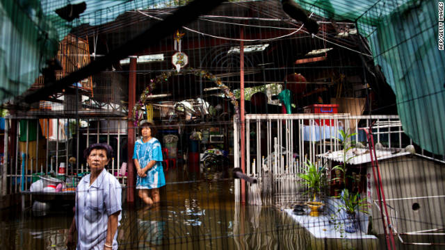 Women stand in a flooded residential area in Bangkok's Chinatown. Overall damage from the floods could top $6 billion, the Thai Finance Ministry said.