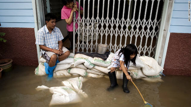 A girl tries to catch fish in floodwaters outside her house Wednesday.
