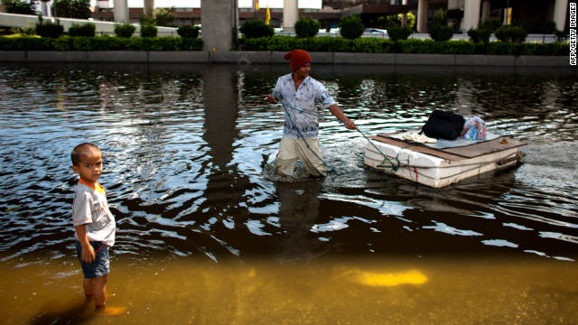 A man pulls a makeshift raft through a flooded street in Bangkok on Wednesday. Floodwaters extend from Rangsit, north of Bangkok, to the Don Muang airport and Yingcharoen Market.
