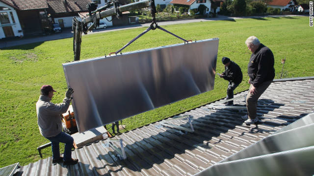 Workers in Wessling, Germany, install solar power modules on the roof of a home.