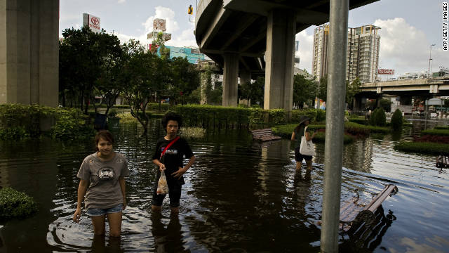 Residents wait for a rescue boat as they evacuate their neighborhood next to the Chao Praya River in Bangkok on Friday.