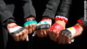 Yemenis women show off their fists paintd in the colors of five national flags: Yemen, Libya, Syria, Tunisia and Egypt.