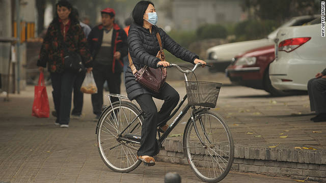 A woman tries to counter poor quality air by wearing a mask as she rides a bicycle in Beijing on October 31, 2011.