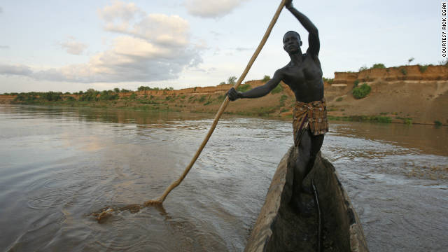 "Kara tribe member Bona Shapo navigates his way across the Omo River in a boat made out of a hollowed log. Shapo says the river is a place where some of the mingi killings take place. ""Sometimes they take the babies out in a boat. Other times, they just take them to the edge of the water and throw them in."""