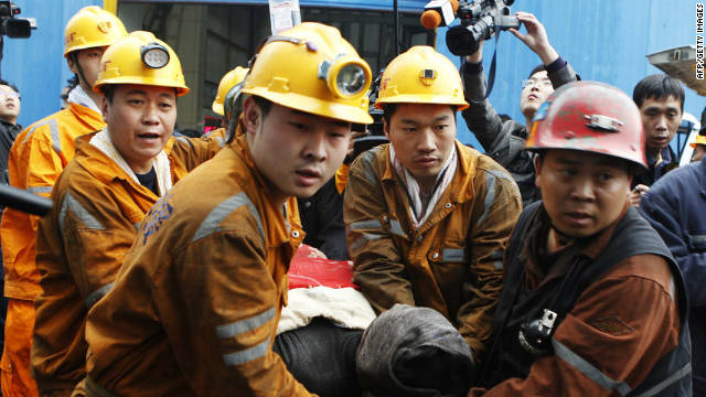 Chinese rescuers carry out one of the rescued miners from the Qianqiu colliery in Henan province.