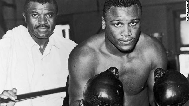 Frazier poses in a fighting stance in the ring with his trainer Eddie Futch behind the ropes in 1968.