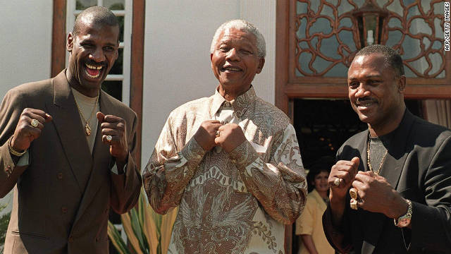 Then South African president Nelson Mandela poses with former heavyweight boxing champions Michael Spinks, left, and Frazier in Pretoria in 1997. 