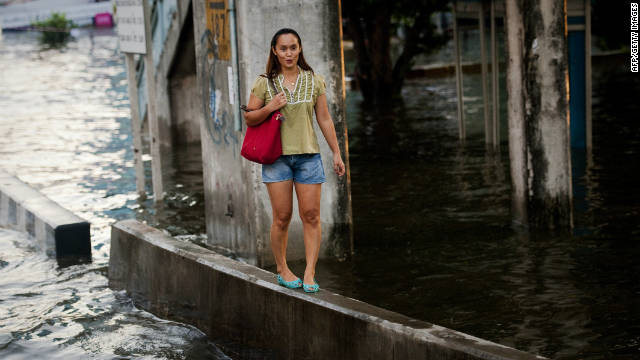 A woman walks along a wall to avoid floodwater in Bangkok, Thailand, November 7.