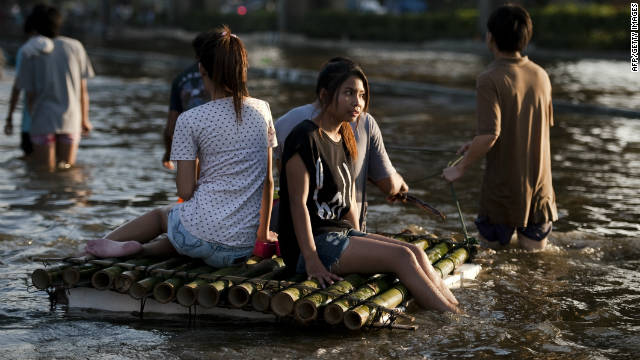 People sit on a bamboo raft to cross the floodwaters in Lat Phrao shopping and business district in Bangkok, November 7.