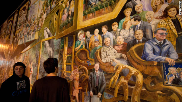 Students pass the mural at the College Bookstore where the portrait of Jerry Sandusky, the former coach accused in the scandal, has been removed and replaced with a blue ribbon.