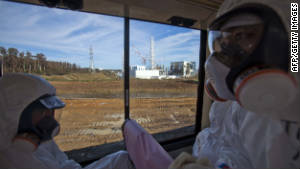 An official from the Tokyo Electric Power Co. (R) and a man, both wearing protective suits and masks, ride on a bus as they pass by the crippled Fukushima Dai-ichi nuclear power station, seen through the window, in Okuma on November 12, 2011. Japan took a group of journalists inside the crippled Fukushima Daiichi nuclear plant for the first time, stepping up its efforts to prove to the world it is on top of the disaster. AFP PHOTO / POOL (Photo credit should read DAVID GUTTENFELDER/AFP/Getty Images)