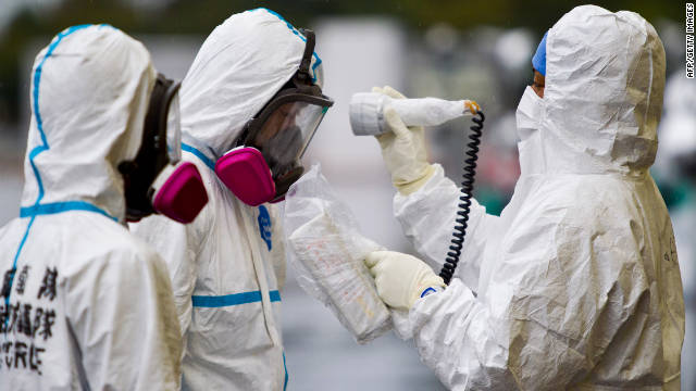 Workers dressed in protective suits and masks are checked for radiation outside a building at J-Village, a soccer training complex now serving as an operation base for those battling Japan's nuclear disaster in Fukushima.