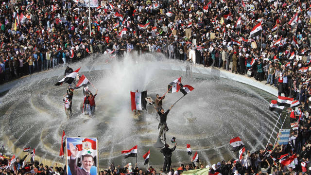 Syrians show their support for President Bashar al-Assad in Damascus on November 13.
