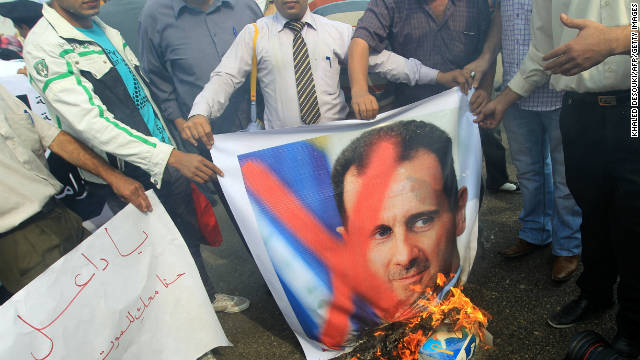 Pro-democracy protesters burn portraits of Syrian President Bashar al-Assad outside the Arab League headquarters in Cairo on November 12.