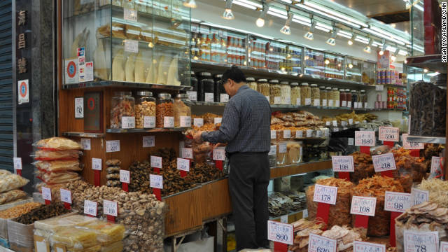 A shop owner works in his dried seafood store, where dried shark fins are displayed in a glass case. 