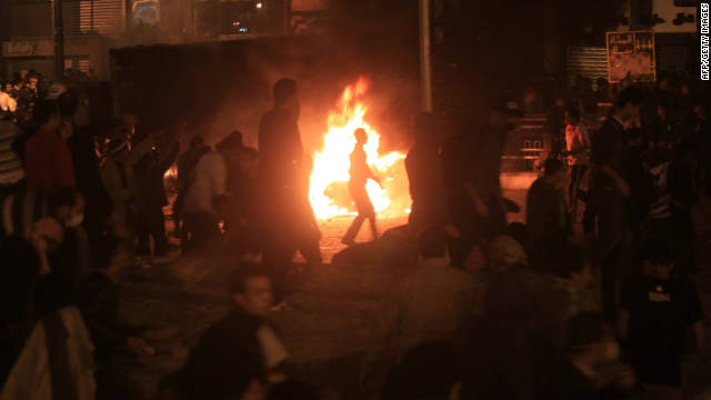 A burning truck illuminates a crowd of protesters in Tahrir Square on Saturday.